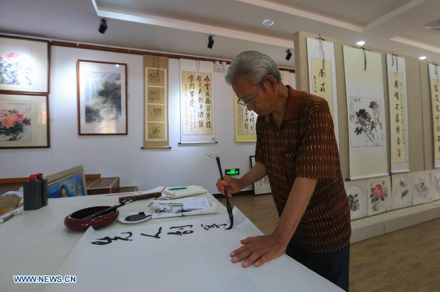 Song Rendou writes Chinese calligraphy in the Muyun'an community of Rongcheng City,east China's Shandong Province, July 5, 2018. The Muyun'an community is famous for painting and is dedicated to boosting tourism based on cultural heritages. (Xinhua/Wang Nan)<br/>