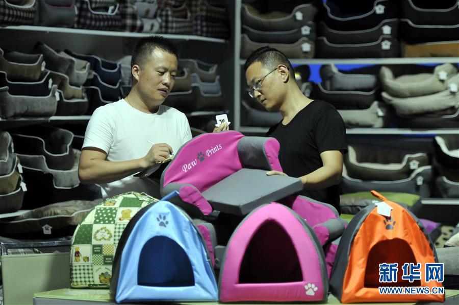 7月4日,在山东省临沂市郯城县马头镇,一家工艺品公司质检员对出口的狗窝进行编码。