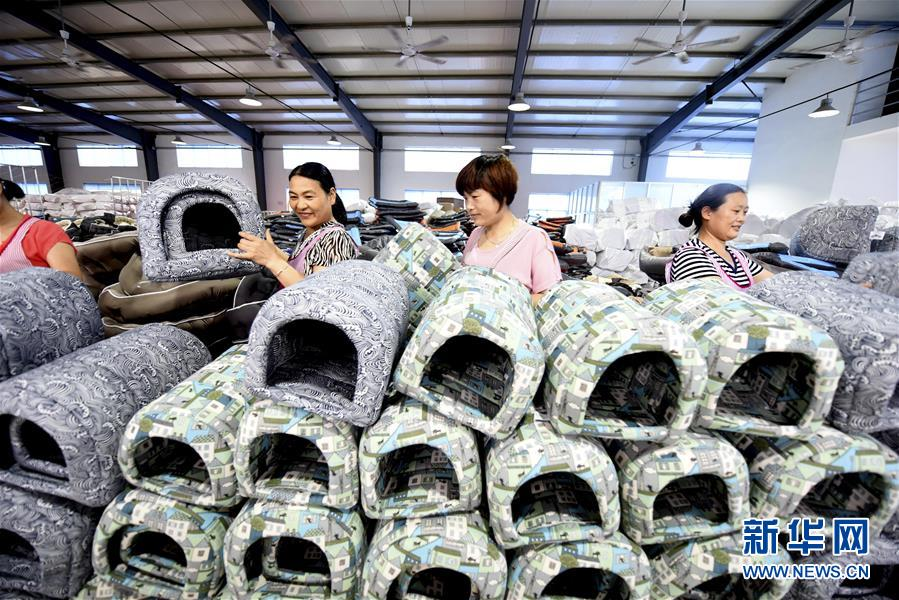 7月4日,在山东省临沂市郯城县马头镇,一家工艺品公司工人在整理出口的狗窝。<br/>