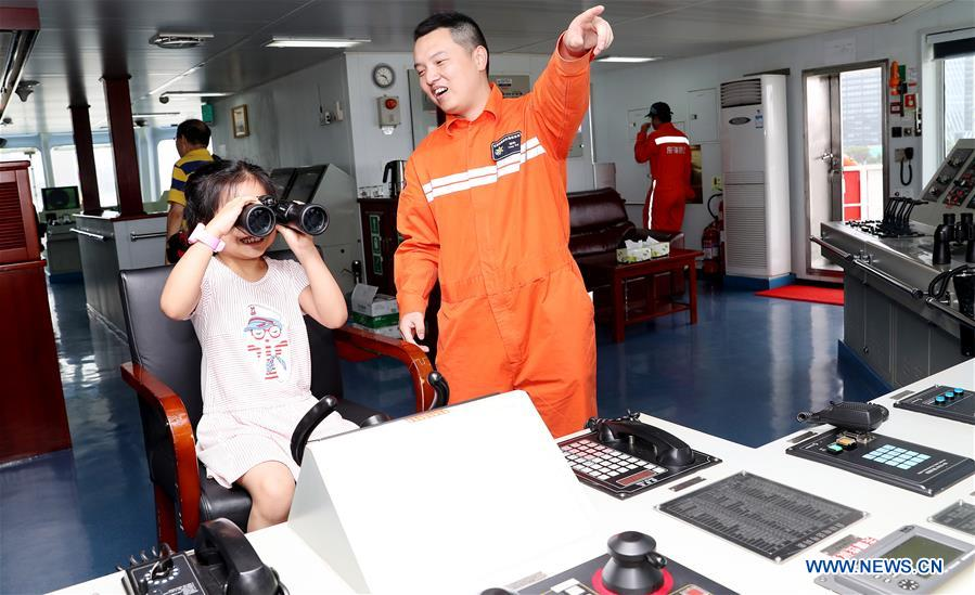 A crew member (R) interacts with a young visitor to the Dong Hai Jiu 101 rescue vessel during a ship open day activity marking the 2018 Maritime Day of China in east China's Shanghai, July 11, 2018. The 2018 Maritime Day of China was observed on Wednesday. (Xinhua/Fang Zhe)<br/>