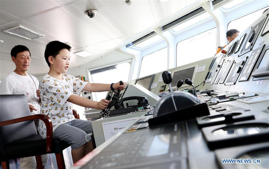A boy sits on the pilot seat aboard the Dong Hai Jiu 101 rescue vessel during a ship open day activity marking the 2018 Maritime Day of China in east China's Shanghai, July 11, 2018. The 2018 Maritime Day of China was observed on Wednesday. (Xinhua/Fang Zhe)