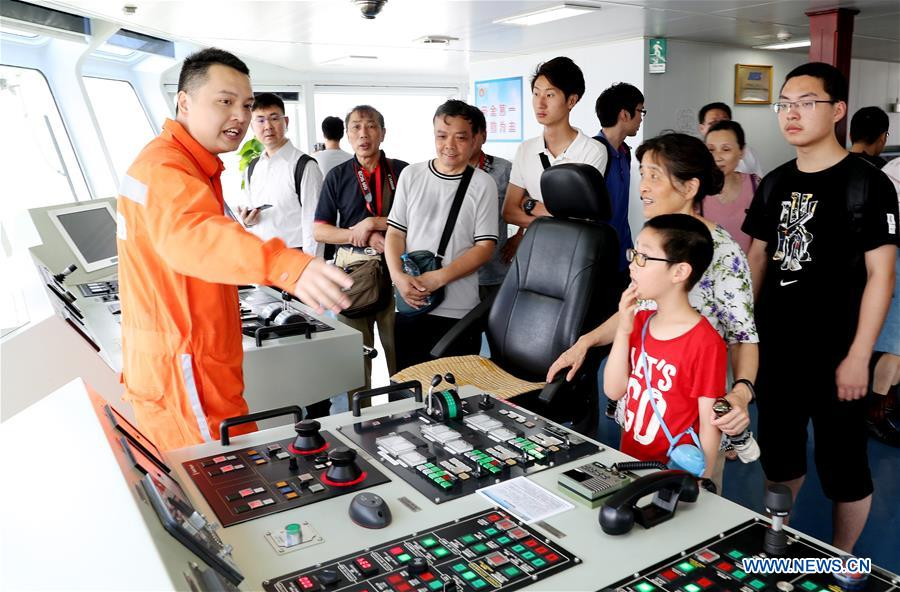 A crew member (1st L) introduces the bridge of the Dong Hai Jiu 101 rescue vessel to visitors during a ship open day activity marking the 2018 Maritime Day of China in east China's Shanghai, July 11, 2018. The 2018 Maritime Day of China was observed on Wednesday. (Xinhua/Fang Zhe)<br/>