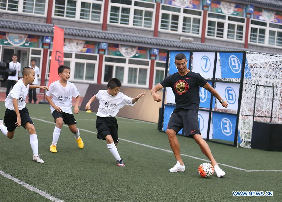 Portuguese football player Cristiano Ronaldo plays football with students as he attends a promotional event in Beijing, China, on July 19, 2018. (Xinhua/Cao Can)<br/>