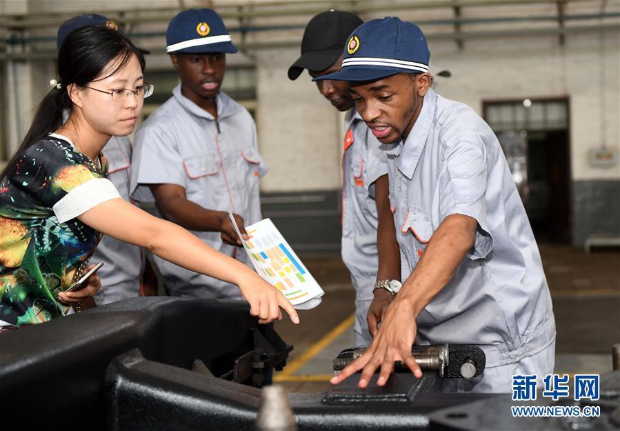 7月24日,留学生散巴斯坦(右一)向技术人员请教。