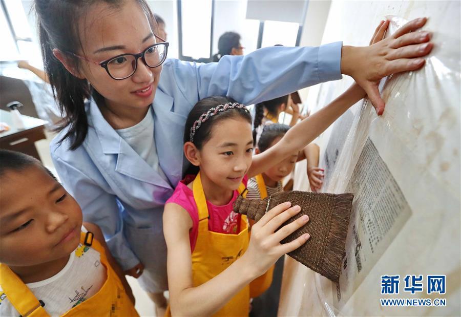 지난 2일 허베이성 친황다오(秦皇島)시 기록보관소 직원이 기록 보관 문화를 체험하러 온 하이강(海港)구 커뮤니티의 어린이들에게 문서 복원 과정을 보여주고 있다. 여름방학 기간 수많은 중국 어린이들이 다양한 방식을 통해 방학을 즐기고 있다.<br/>