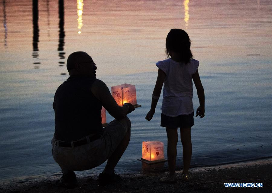 A man prepares to release a water lantern during a water lantern festival at National Habor in Maryland, the United States, Aug. 4, 2018. Lanterns were set afloat to glow on the Potomac River for the Water Lantern Festival on Saturday, creating a spectacular and glistening light display. (Xinhua/Liu Jie)<br/>