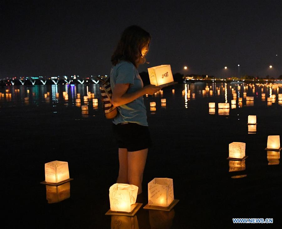 A girl holds a water lantern during a water lantern festival at National Habor in Maryland, the United States, Aug. 4, 2018. Lanterns were set afloat to glow on the Potomac River for the Water Lantern Festival on Saturday, creating a spectacular and glistening light display. (Xinhua/Liu Jie)