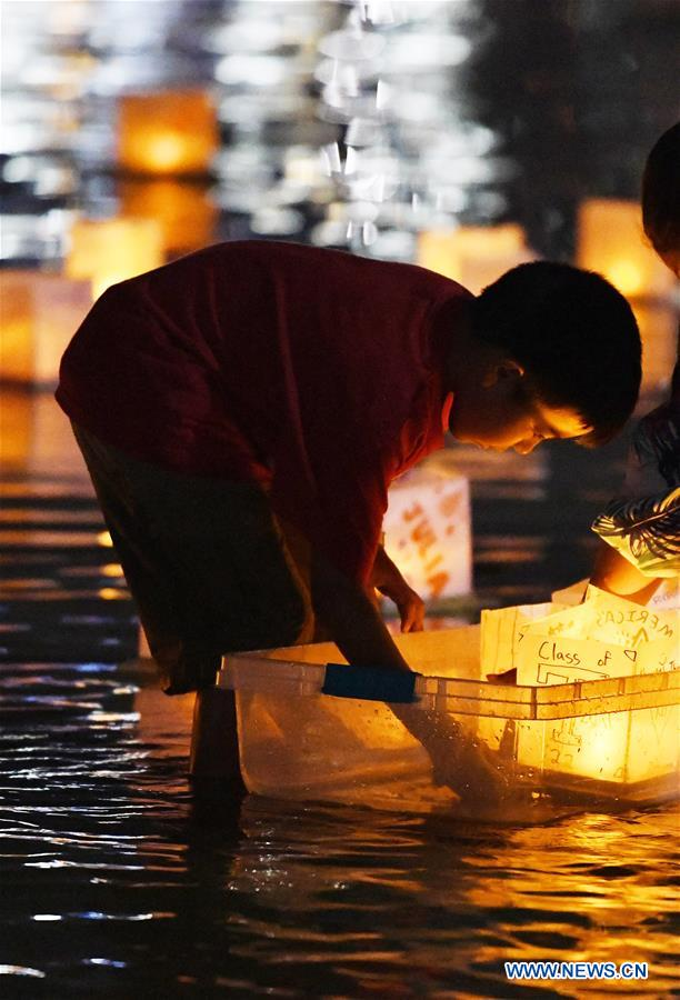 A boy releases a water lantern during a water lantern festival at National Habor in Maryland, the United States, Aug. 4, 2018. Lanterns were set afloat to glow on the Potomac River for the Water Lantern Festival on Saturday, creating a spectacular and glistening light display. (Xinhua/Liu Jie)<br/>