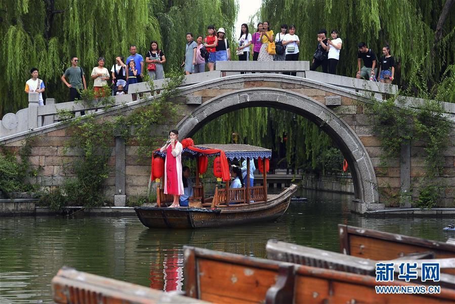 8月4日,在山东省枣庄市台儿庄古城景区,工作人员在游船上为游客表演陶笛。