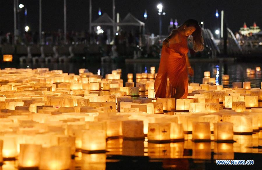 A woman walks among floating water lanterns during a water lantern festival at National Habor in Maryland, the United States, Aug. 4, 2018. Lanterns were set afloat to glow on the Potomac River for the Water Lantern Festival on Saturday, creating a spectacular and glistening light display. (Xinhua/Liu Jie)<br/>