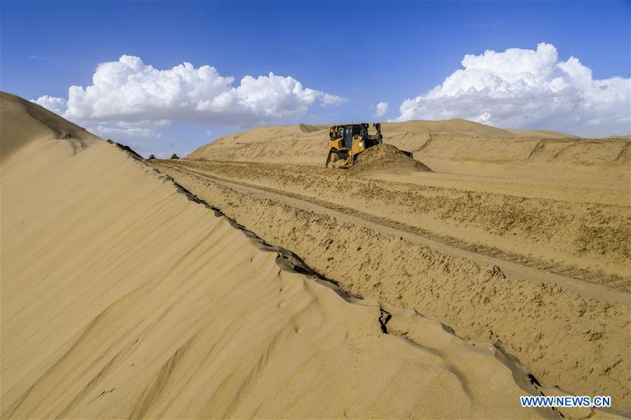 Photo taken on July 5, 2018 shows the construction site of the desert road linking Yuli County to Qiemo County in northwest China's Xinjiang Uygur Autonomous Region. As an important link of the Silk Road Economic Belt, Xinjiang is speeding up the development of transportation and logistics to connect east and west. By the end of 2017, the total length of roads in Xinjiang reached 186,000 km, with 4,578 km of expressways. (Xinhua/Hu Huhu)<br/>