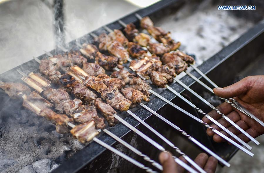 A cook makes grilled lamb chops in Changji, northwest China's Xinjiang Uygur Autonomous Region, April 28, 2017. (Xinhua/Zhao Ge)<br/>