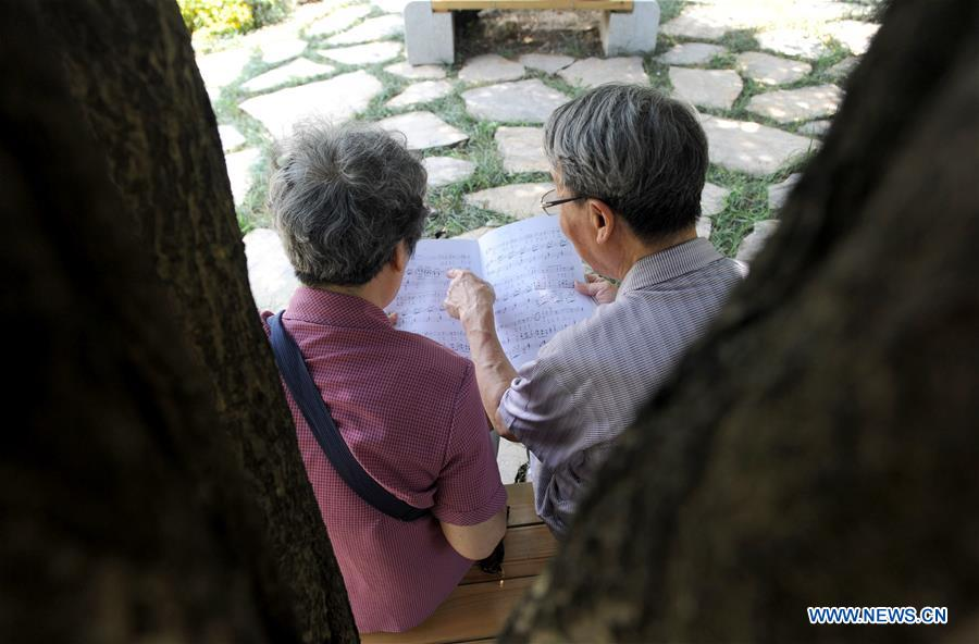 Liu Xingren (R), accompanied by his wife Sun Yiqing, looks at music score during a break of a contest of Huanglong music festival in Zhangjiajie, central China's Hunan Province, Aug. 14, 2018. The 82-year-old Liu is a retired lawyer. He once organized an amateur chorus and orchestra. As a music enthusiast, Liu practices singing in his spare time. His wife Sun Yiqing, 76, is a retired teacher. Liu Xingren was accompanied on several singing contests in Beijing and Tianjin by his wife. The aged couple has a wish to continue to pursue their singing dream in the future. (Xinhua/Wei Hai)