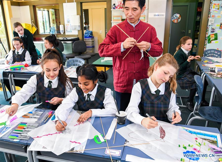 Guo Hongli, a kite specialist from China's kite city of Weifang in east China's Shandong Province, teaches students kite-making skills in Samuel Marsden Collegiate School, Wellington, New Zealand, on Sept. 12, 2018. Students of Samuel Marsden Collegiate School learned how to make traditional Chinese kites at an event organized by New Zealand China Cultural Center here on Wednesday. (Xinhua/Guo Lei)<br/>