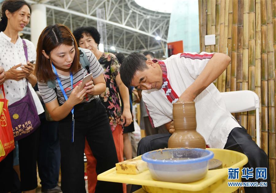 9月13日,观众在博览会上参观龙山黑陶的制作过程。<br/>