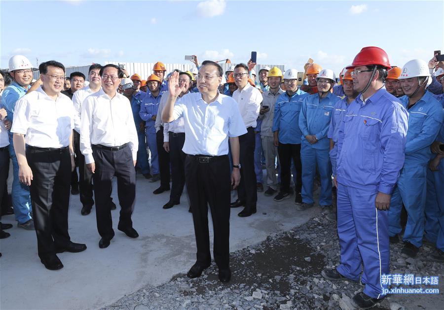 27日、魚山島で建設中の民営企業の株式投資による世界規模の総合的な大型石油化学産業プロジェクトを視察する李克強総理。(杭州=新華社記者/龐興雷)<br/>  李克強氏は国有、民営、外資系企業と金融機関の代表が参加する座談会で、中国には巨大な市場と人的資源の潜在力があり、われわれには困難や課題に対応し、経済の安定を持続させる自信と能力があると表明。ビジネス環境を改善する工夫をし、減税と費用引き下げを一段と強化し、企業融資や物流などのコストを引き下げ、特に零細企業に対して政策支援を実施しなければならないと強調した。