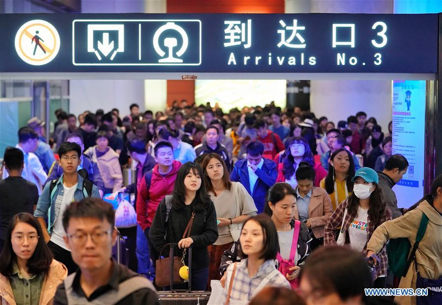 Passengers walk out of an arrival gate at Beijing South Railway Station in Beijing, capital of China, Oct. 7, 2018. A travel peak is seen around China on Sunday, the last day of the week-long National Day holidays. (Xinhua/Xing Guangli)