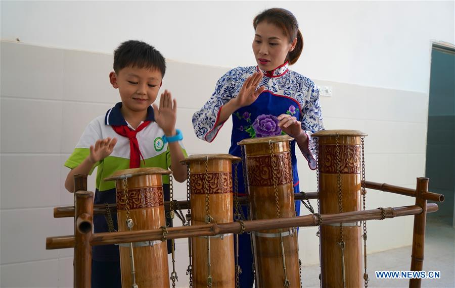A member from a local bamboo music band teaches a student to play a bamboo musical instrument in Chongyi County, east China's Jiangxi Province, Oct. 8, 2018. Members from the bamboo music band are invited to a primary school regularly to give lessons to students on bamboo musical instruments. (Xinhua/Hu Chenhuan)