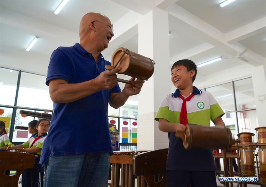A member from a local bamboo music band teaches a student to play a bamboo musical instrument in Chongyi County, east China's Jiangxi Province, Oct. 8, 2018. Members from the bamboo music band are invited to a primary school regularly to give lessons to students on bamboo musical instruments. (Xinhua/Hu Chenhuan)<br/>
