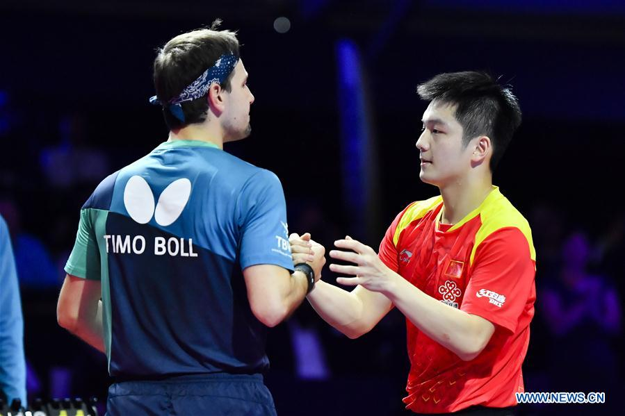 Fan Zhendong of China (R) shakes hands with Timo Boll of Germany after the final match of the 2018 ITTF Men's World Cup in Chessy, France on Oct. 21, 2018. Fan Zhendong won 4-1 and claimed the title. (Xinhua/Chen Yichen)