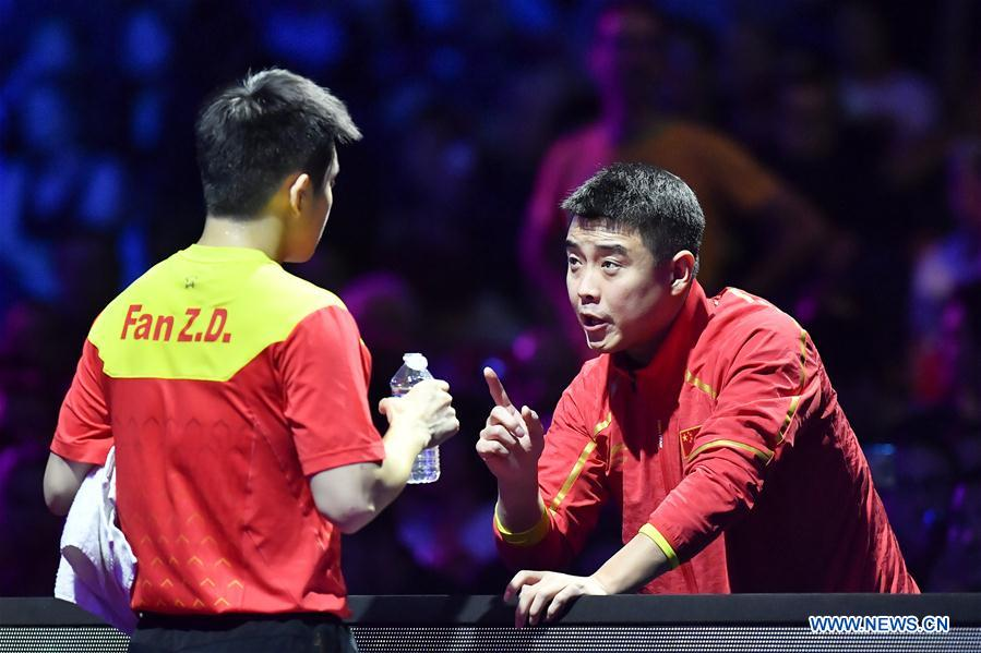 Fan Zhendong (L) of China talks to his coach Wang Hao during the final match against Timo Boll of Germany at the 2018 ITTF Men's World Cup in Chessy, France on Oct. 21, 2018. Fan Zhendong won 4-1 and claimed the title. (Xinhua/Chen Yichen)<br/>