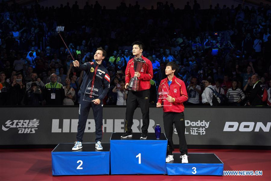 Silver medalist Timo Boll of Germany, gold medalist Fan Zhendong and bronze medalist Lin Gaoyuan of China (L to R) pose for a selfie during the awarding cermeony of the 2018 ITTF Men's World Cup in Chessy, France on Oct. 21, 2018. (Xinhua/Chen Yichen)<br/>