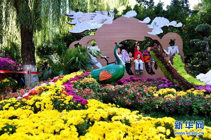 어린이들이 지난(濟南)시 바오투취안(趵突泉•표돌천) 공원 국화 조형물 앞에서 사진을 찍고 있다. [촬영: 궈쉬레이(郭緒雷) 기자]