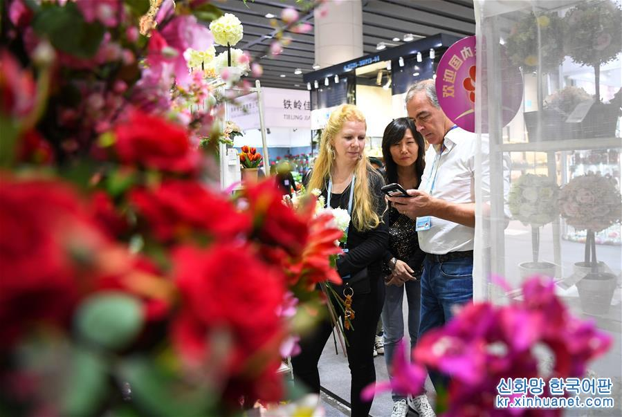 바이어가 제124회 광저우 상품교역회에서 조화 가격을 흥정하고 있다(10월 23일 촬영). [촬영/ 신화사 기자 덩화(鄧華)]