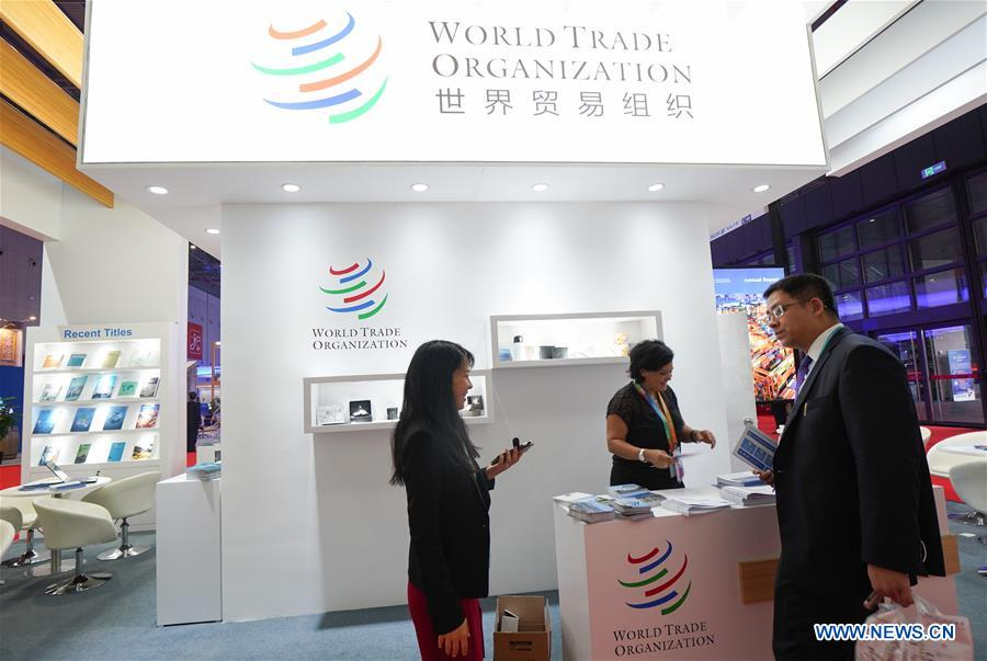 People visit the booth of World Trade Organization at the first China International Import Expo (CIIE) in Shanghai, east China, Nov. 5, 2018. A total of 82 countries and three international organizations showcased their achievements in economic and trade development as well as competitive products at 71 booths in the Country Pavilion for Trade and Investment at the CIIE. (Xinhua/Wang Jianhua)<br/>