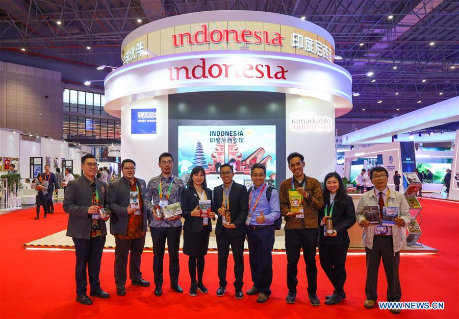 People pose for photos with the Indonesia pavilion during the first China International Import Expo (CIIE) in Shanghai, east China, Nov. 5, 2018. A total of 82 countries and three international organizations showcased their achievements in economic and trade development as well as competitive products at 71 booths in the Country Pavilion for Trade and Investment at the CIIE. (Xinhua/Liu Dawei)<br/>