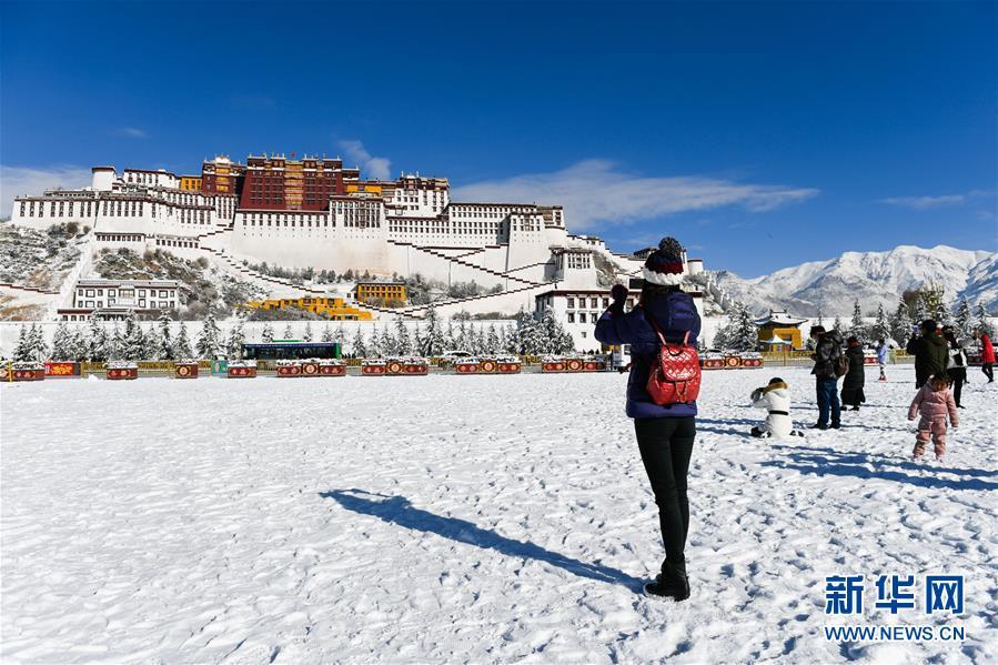 12月19日,一名游客在布达拉宫广场上拍摄雪景。 12月18日,西藏拉萨市迎来今年入冬以来的首场降雪。19日清晨,拉萨雪后初霁,处处银装素裹,尽显雪域高原之美。 新华社记者刘东君摄<br/>