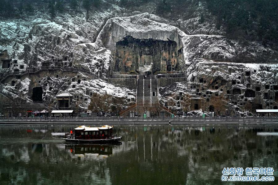 1월 9일, 유람선 한척이 뤄양(洛陽) 룽먼석굴(龍門石窟) 펑셴사(奉先寺) 앞 수면위를 지나가고 있다. 당일, 눈 내린 후의 허난(河南) 뤄양 룽먼석굴 관광구역은 온통 은빛으로 단장되어 마치 한 폭의 서서히 펼쳐진 수묵화를 방불케 했다. [촬영/ 신화사 기자 리안(李安)]<br/>