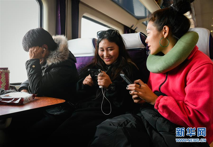 <br/>   大学生刚措(右)和桑旦措姆(中)放寒假乘坐Z6802次列车回老家那曲(1月11日摄)。<br/>