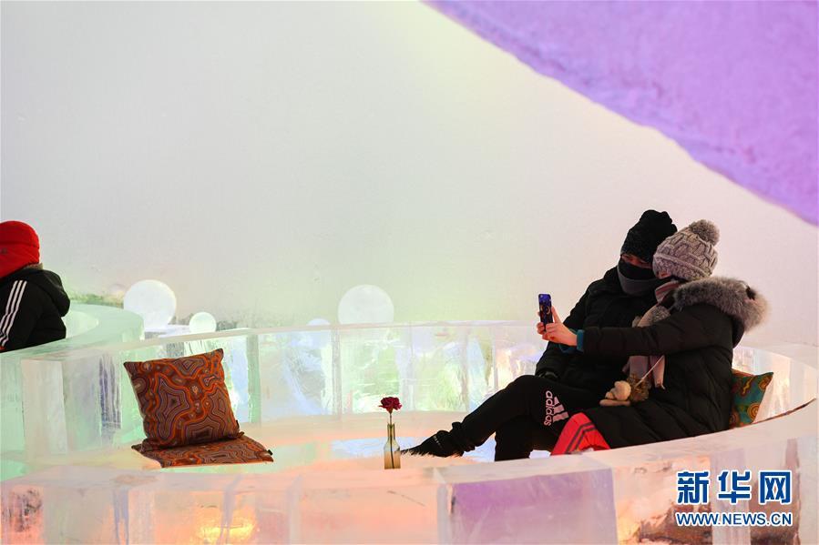 <br/>   1月17日,游客在哈尔滨冰雪大世界园区的冰酒吧拍照。<br/>