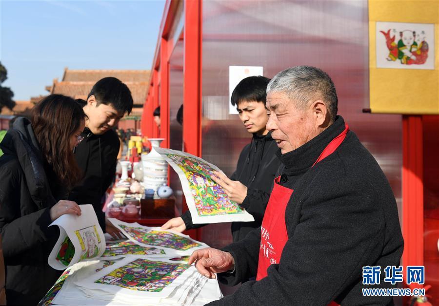 <br/>   1月28日,年画艺人尹国全(右一)向游客介绍年画。
