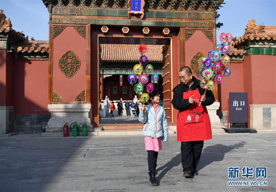 """1月28日,风车制作艺人王国华(右)向一名小女孩介绍风车。 当日,""""中华老字号故宫过大年展""""在北京故宫开幕,来自北京、天津、山东、山西等地的150家单位参展。活动将持续至2月10日(正月初六),期间观众可凭故宫博物院门票免费参观。"""