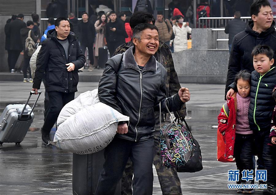 1月30日,在郑州火车站东广场,一名旅客拿着行李进站乘车。春节临近,在郑州火车站,旅客脸上的笑容给返乡旅途增添了温暖与轻松。<br/>