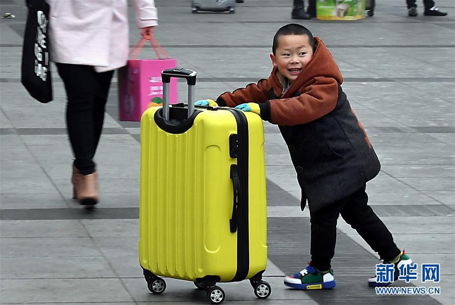 <br/>   1月30日,在郑州火车站东广场,一名小朋友推着行李箱准备进站乘车。<br/>