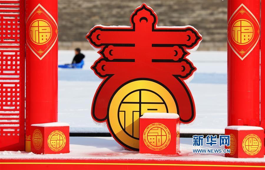 1月31日,在山东省临沂市郯城县一处春节景观附近,一名小男孩在雪地里玩耍。