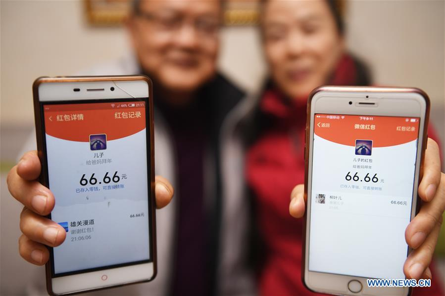Ms. Sun and her husband show digital New Year red packets sent from their son by mobile program Wechat in Fuzhou, capital of southeast China's Fujian Province, Feb. 3, 2019. (Xinhua/Song Weiwei)<br/>