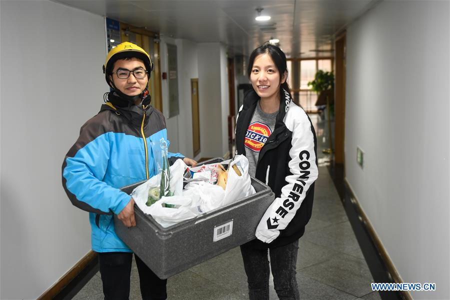 Zhou Xiaoyu,(R) takes fresh ingredients for family reunion dinner on Chinese New Year Eve from a courier in Hangzhou, east China's Zhejiang Province, Feb. 3, 2019. (Xinhua/Huang Zongzhi)<br/>