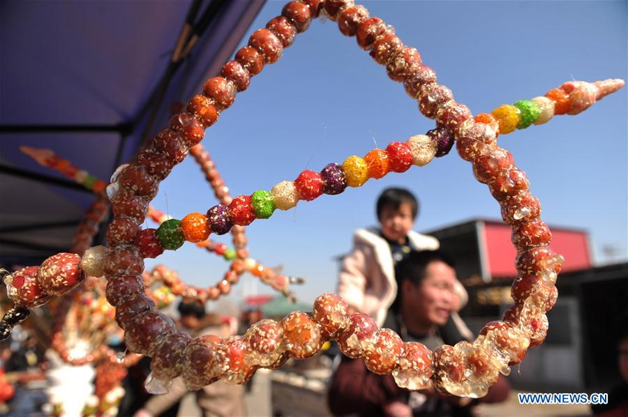 Tourists walk past booths selling tanghulu, a traditional Chinese snack of candied fruit, during an activity to greet the upcoming Lantern Festival in Lihua Village of Renqiu, north China's Hebei Province, Feb. 17, 2019. The traditional Chinese Lantern Festival falls on Feb. 19 this year. (Xinhua/Mu Yu)<br/>