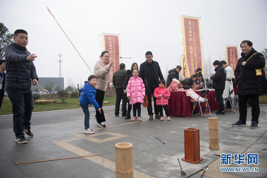<br/>   3月3日,游客在菰城村体验投壶游戏。