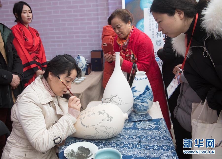 3月3日,人们在菰城村观看陶艺家绘制青瓷花瓶。当日,第五届菰城文化旅游节在浙江省湖州市吴兴区道场乡菰城村开幕,吸引游客前来体味民俗文化。<br/>