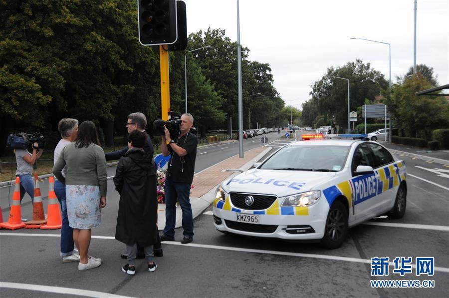 3月16日,在新西兰克赖斯特彻奇市,记者在枪击案现场封锁线附近采访市民。新西兰南岛克赖斯特彻奇市15日下午发生一起枪击案,造成49人死亡、40余人入院接受治疗。 新华社记者卢怀谦摄<br/>