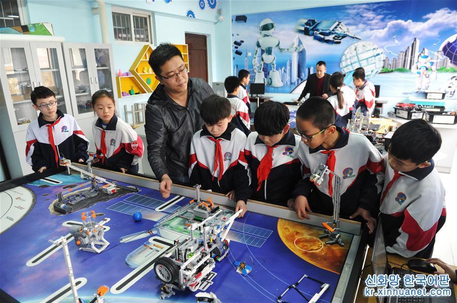 3월28일, 허베이성 런추(任丘)시 실험소학의 교사들이 학생들에게 로봇 조작을 지도하고 있다. 최근 허베이성 런추시는 학교에서 과학기술 교육을 추진해 관할구 내 여러 초중등학교에서 비행기 모형, 로봇, 라디오 등 과목과 취미반을 개강했다. 전문 교사들이 수업을 통해 학생들의 학습과 창작, 작품 전시를 지도해 학생들의 혁신창조 의식과 과학탐색 정신을 고취하고 있다. [촬영/신화사 기자 머우위(牟宇)]<br/>