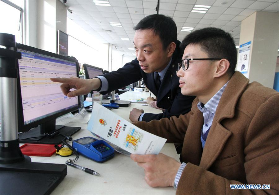 A staff (L) explains to a taxpayer about a new policy on VAT reduction at a local tax bureau in Yongnian District of Handan, north China's Hebei Province, April 1, 2019. Starting on April 1, companies that are subject to the 16-percent VAT rate on their taxable sales or imported goods will enjoy a 13-percent VAT rate, while those who are subject to the 10-percent VAT rate will only need to pay 9 percent, reads a Ministry of Finance statement. (Xinhua/Hu Gaolei)<br/>