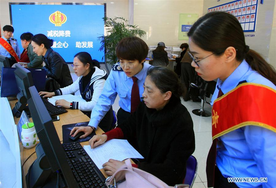 Staff members help citizens with taxpaying at a local administrative service center in Huancui District of Weihai, east China's Shandong Province, April 1, 2019. Starting on April 1, companies that are subject to the 16-percent VAT rate on their taxable sales or imported goods will enjoy a 13-percent VAT rate, while those who are subject to the 10-percent VAT rate will only need to pay 9 percent, reads a Ministry of Finance statement. (Xinhua/Zhu Chunxiao)