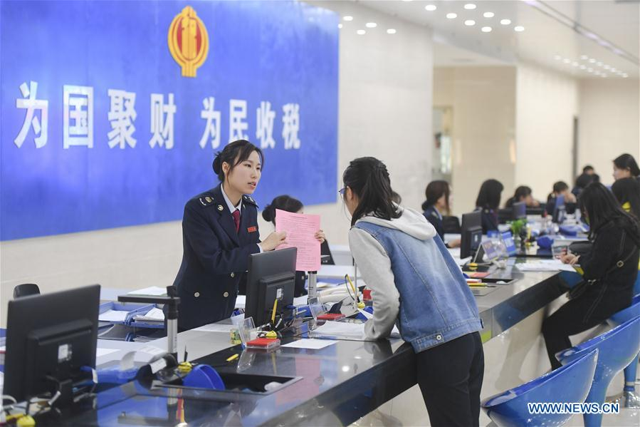 A staff (L) explains to a taxpayer about a new policy on VAT reduction at a local tax bureau in Fengze District of Quanzhou, southeast China's Fujian Province, April 1, 2019. Starting on April 1, companies that are subject to the 16-percent VAT rate on their taxable sales or imported goods will enjoy a 13-percent VAT rate, while those who are subject to the 10-percent VAT rate will only need to pay 9 percent, reads a Ministry of Finance statement. (Xinhua/Song Weiwei)<br/>