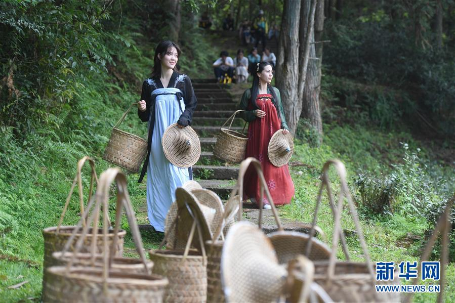<br/>   4月9日,在武夷山市天心村莲花峰下,游客手提传统采茶工具参加活动。<br/>
